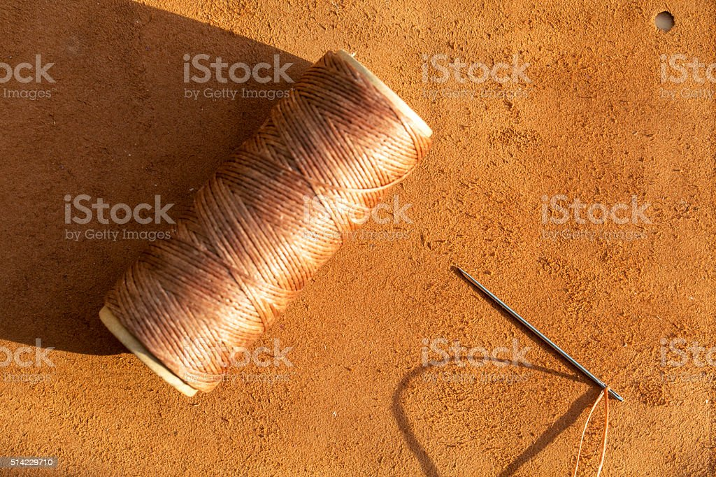 leather materials and thread reel stock photo