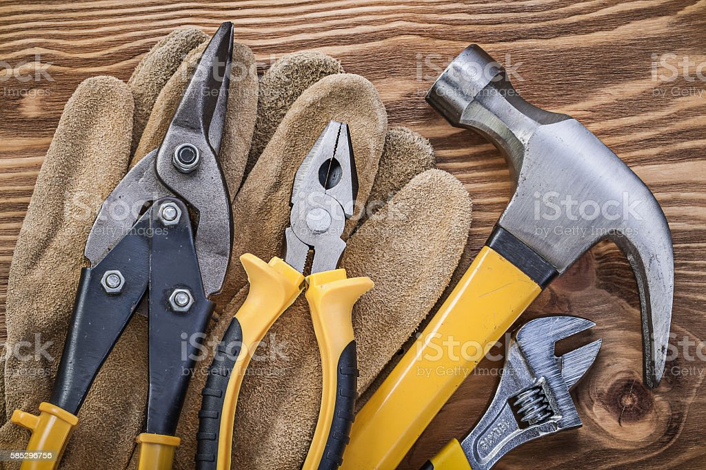 Leather protective gloves claw hammer pliers tin snips adjustabl stock photo