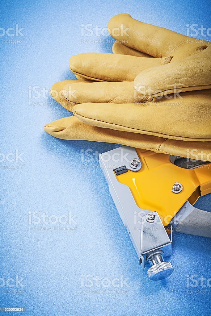 Leather protective gloves yellow construction stapler on blue ba stock photo