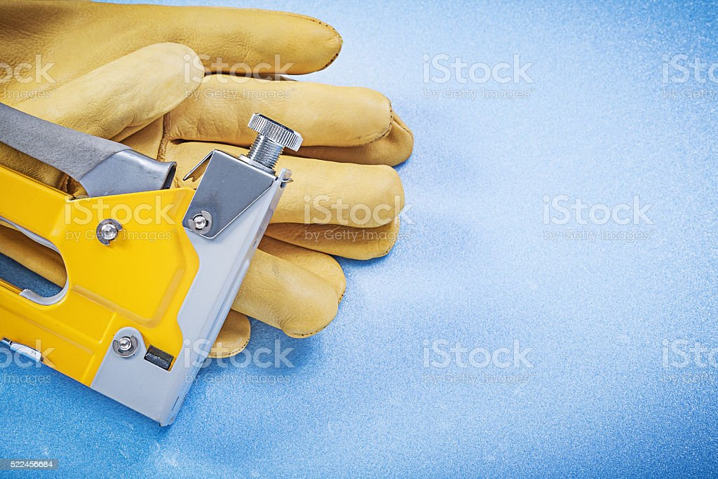 Leather safety gloves yellow construction stapler on blue backgr stock photo