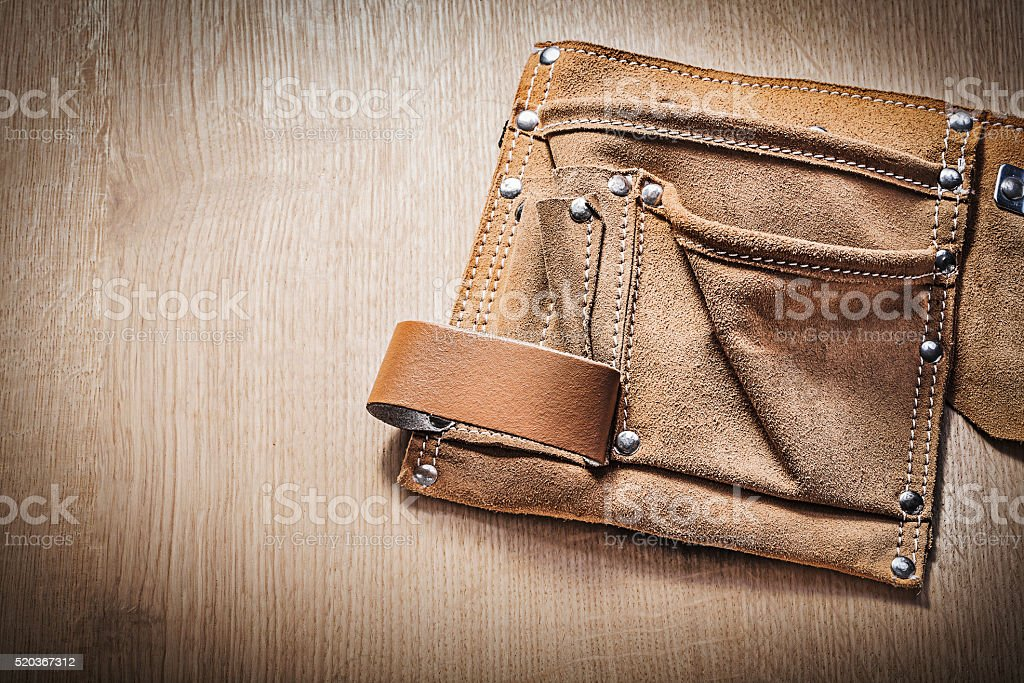 Leather tool belt for building tooling on wooden board stock photo