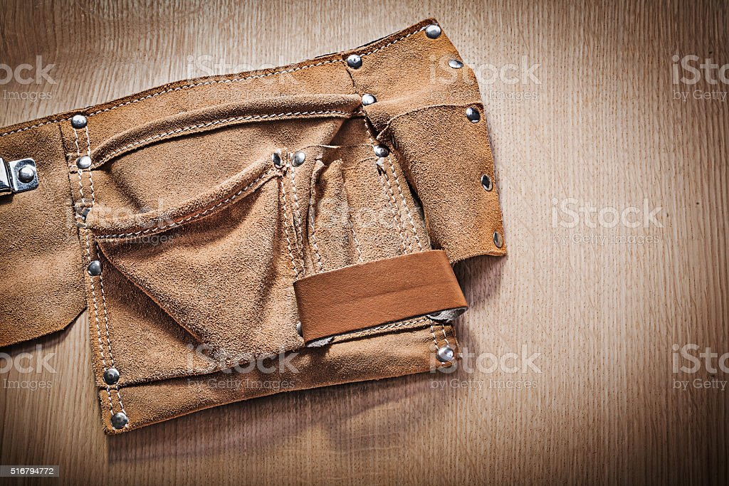 Leather tool belt for construction tooling on wooden board stock photo