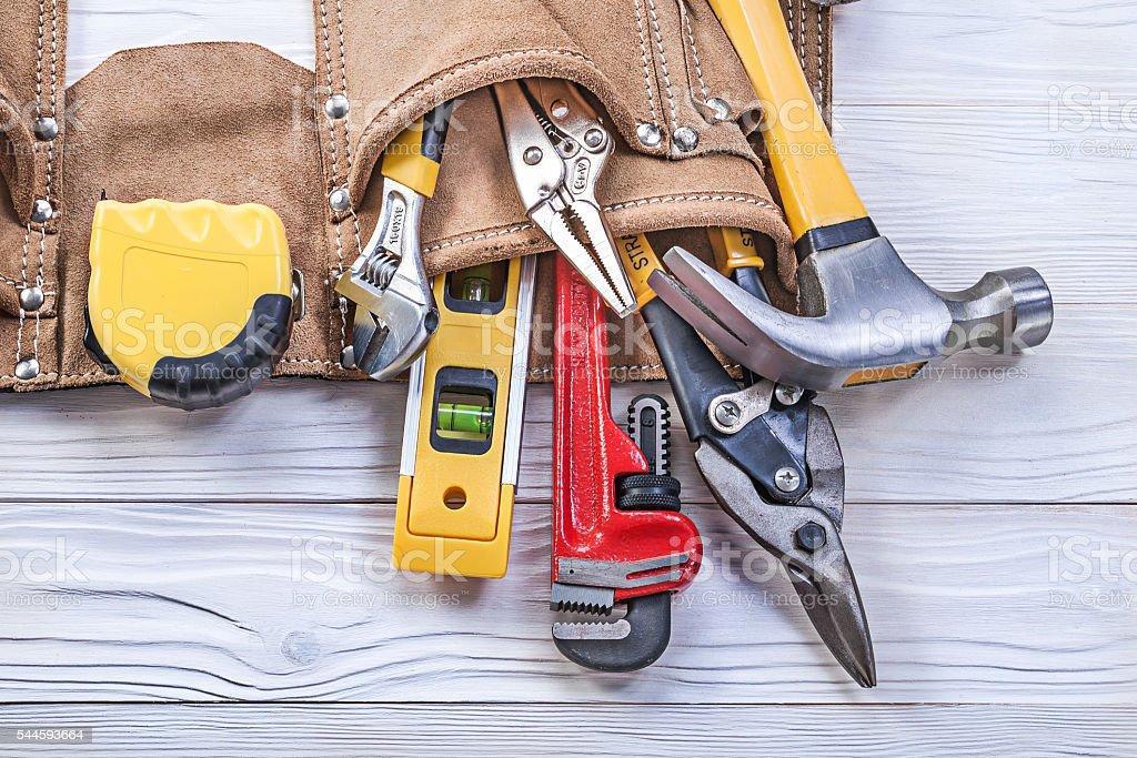 Leather tool belt pliers construction level tape measure monkey stock photo