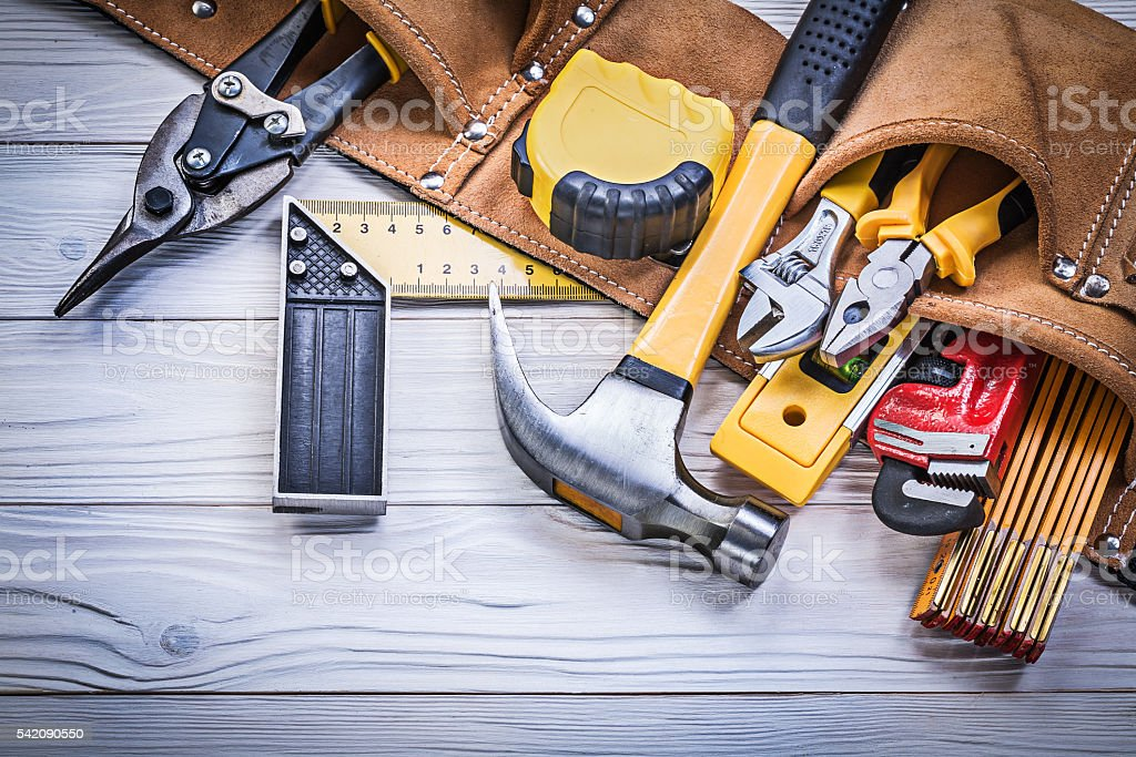 Leather tool belt with construction tooling on wooden board main stock photo