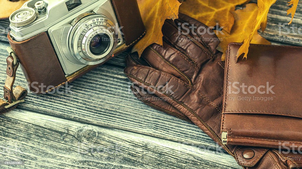 Leather wallet and gloves with vintage camera over wooden backgr stock photo