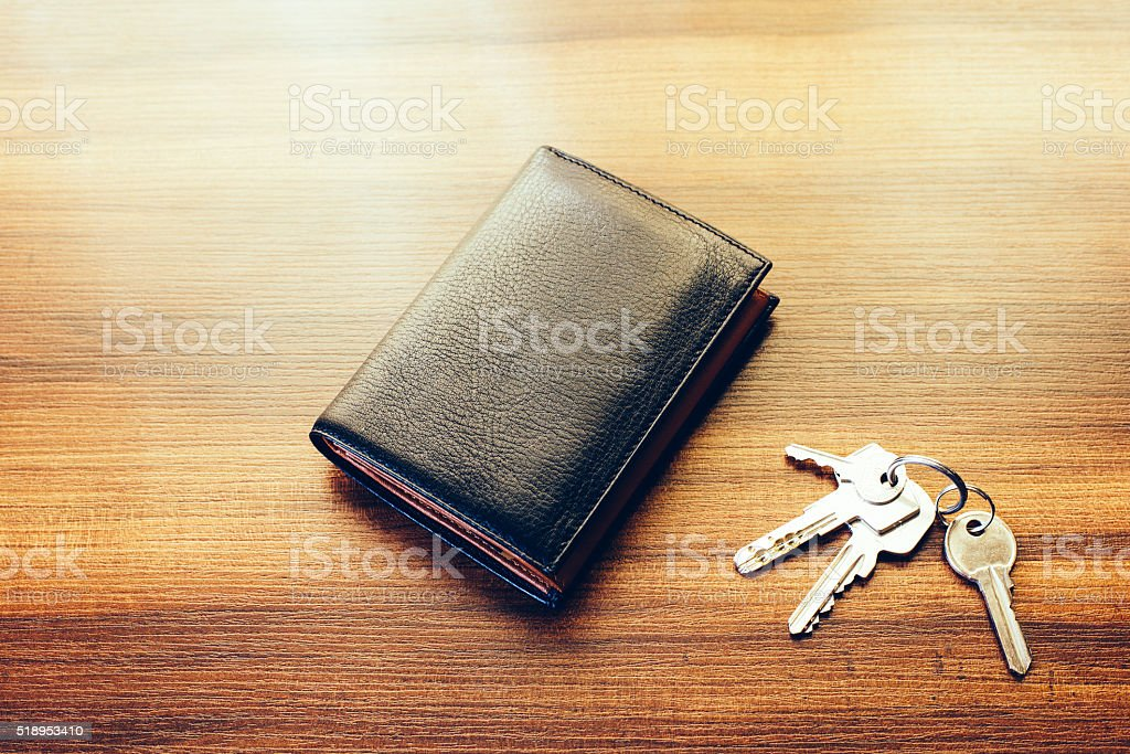 Leather wallet and keys on wooden table stock photo