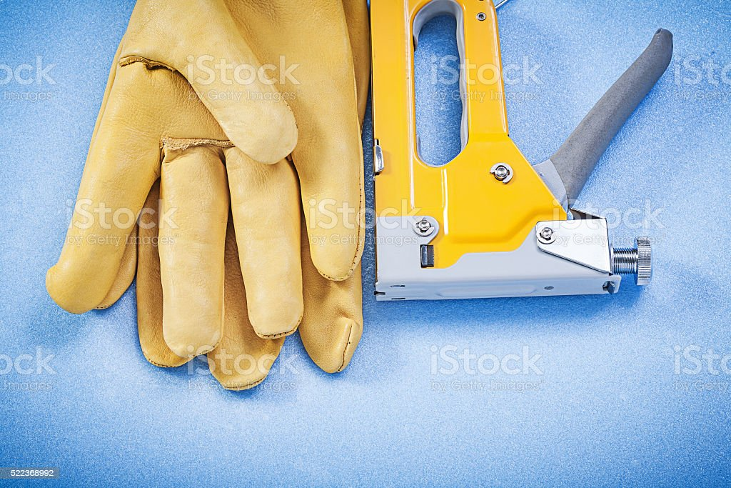 Leather working gloves yellow construction staple on blue backgr stock photo
