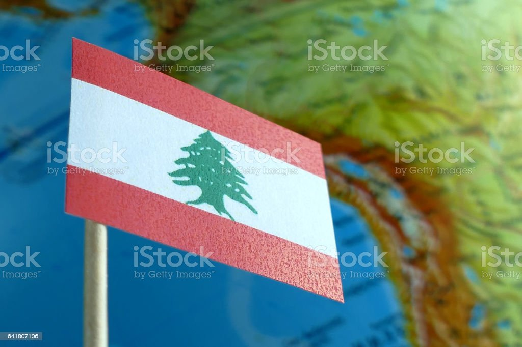 Lebanon flag with a globe map as a background macro stock photo