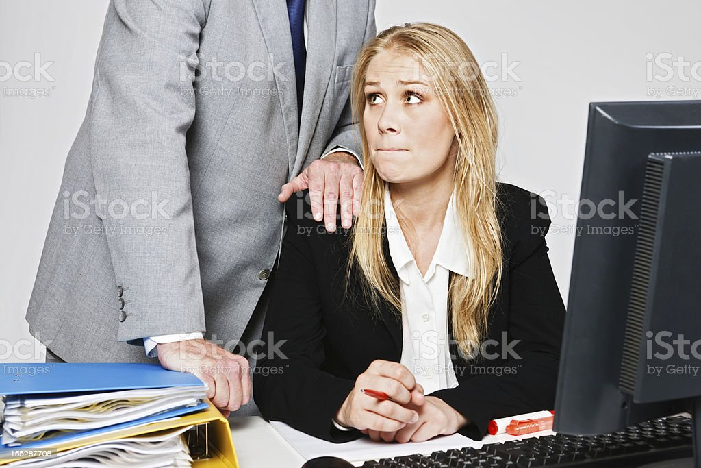 Lecherous businessman harasses helpless young blonde businesswoman stock photo
