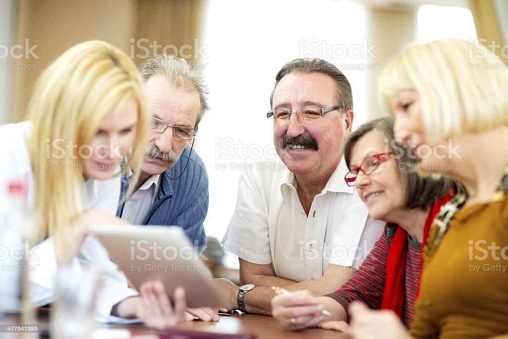 lecturer demonstrates  use of digital tablet to seniors group stock photo