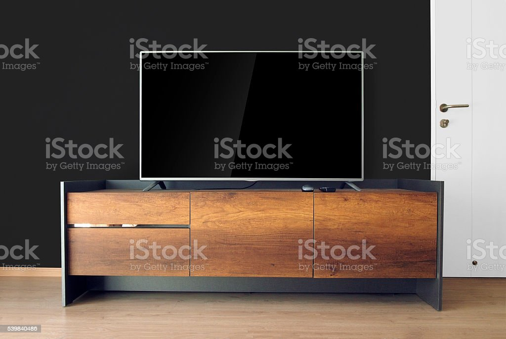 Led TV on TV stand with black wall stock photo