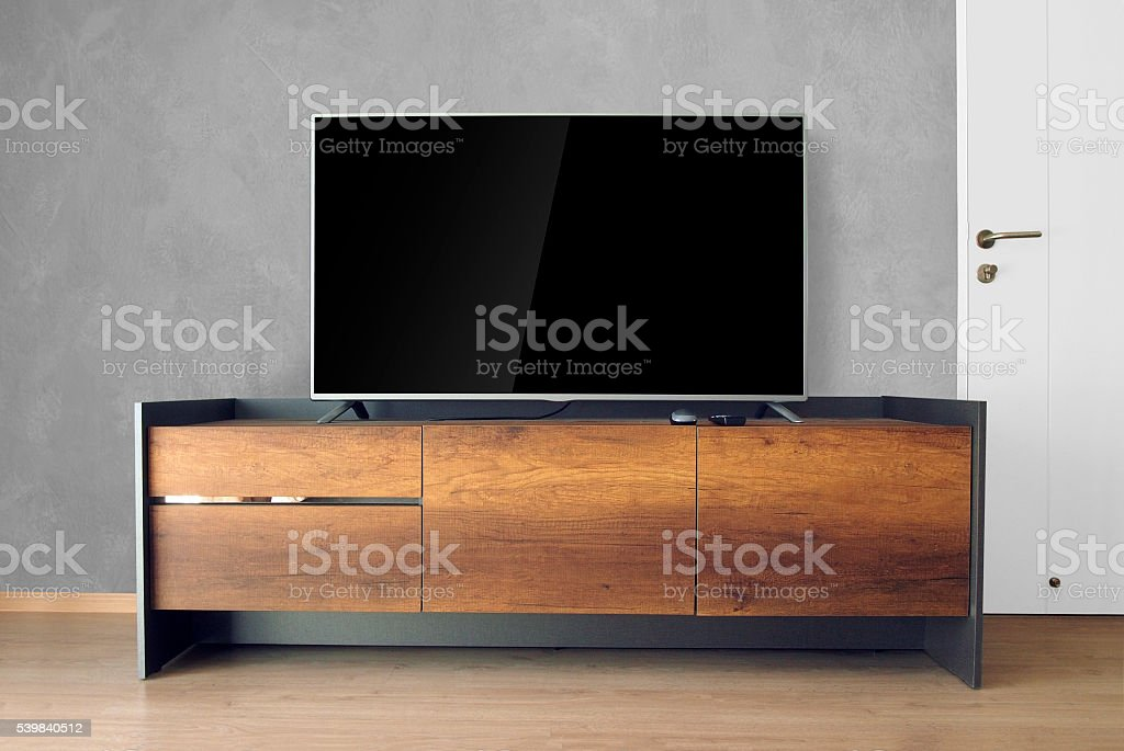 Led TV on TV stand with concrete wall stock photo