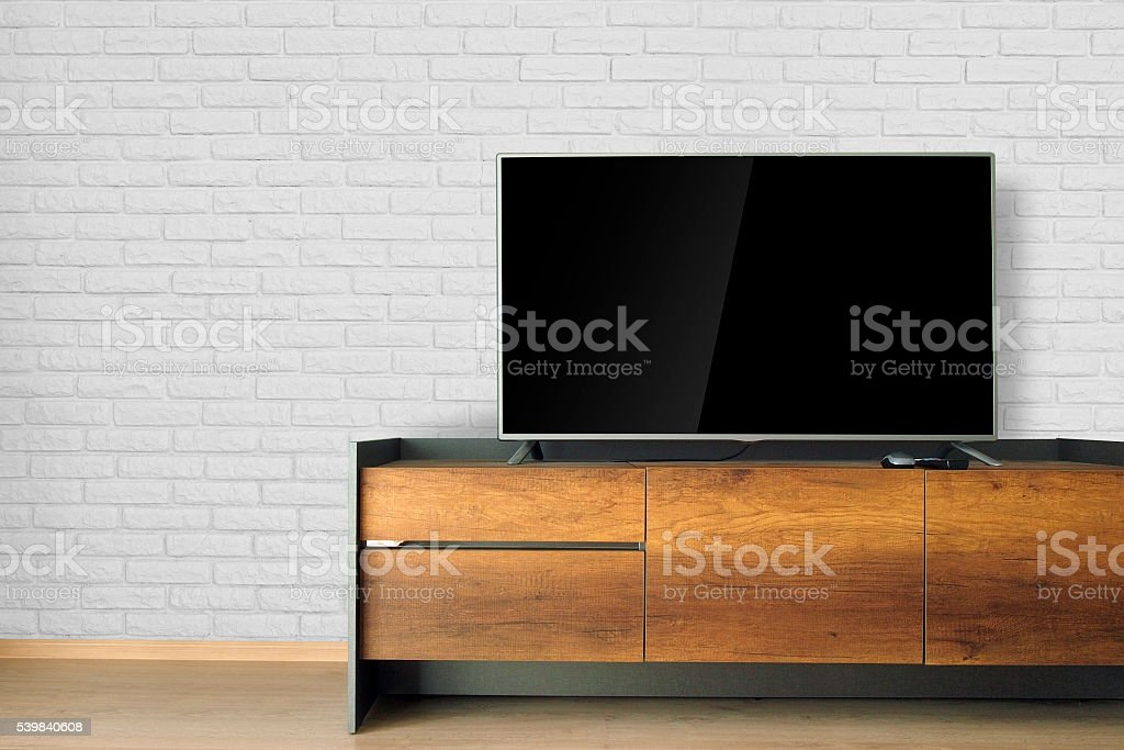 Led TV on TV stand with white brick wall stock photo