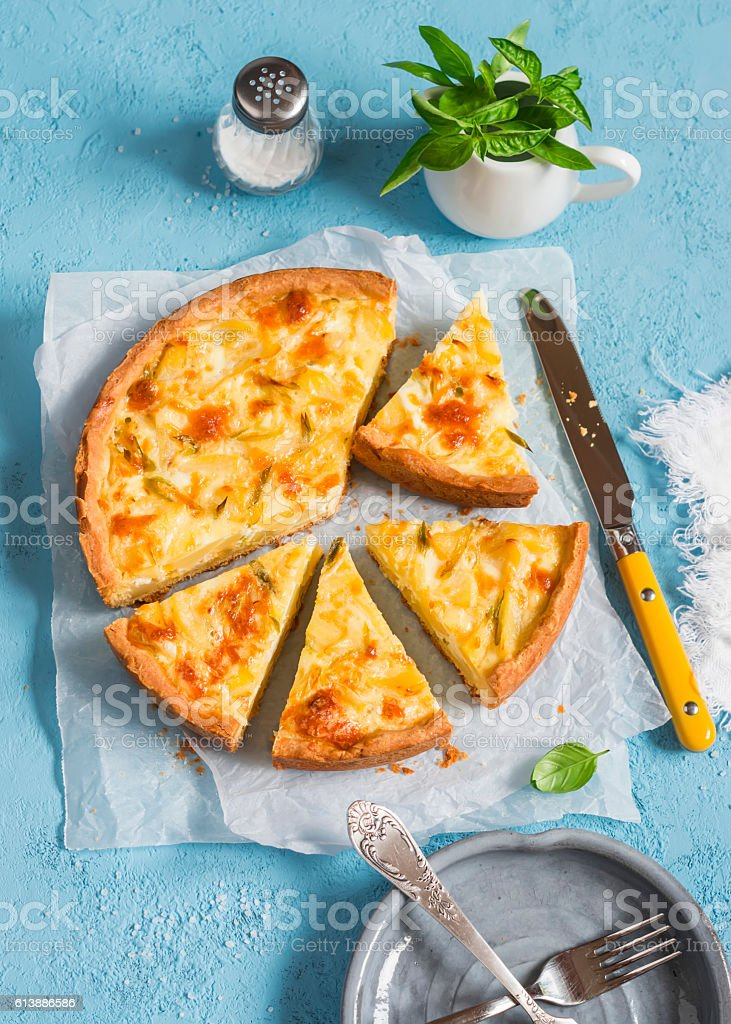 Leek, potato and cheese pie on a blue background stock photo