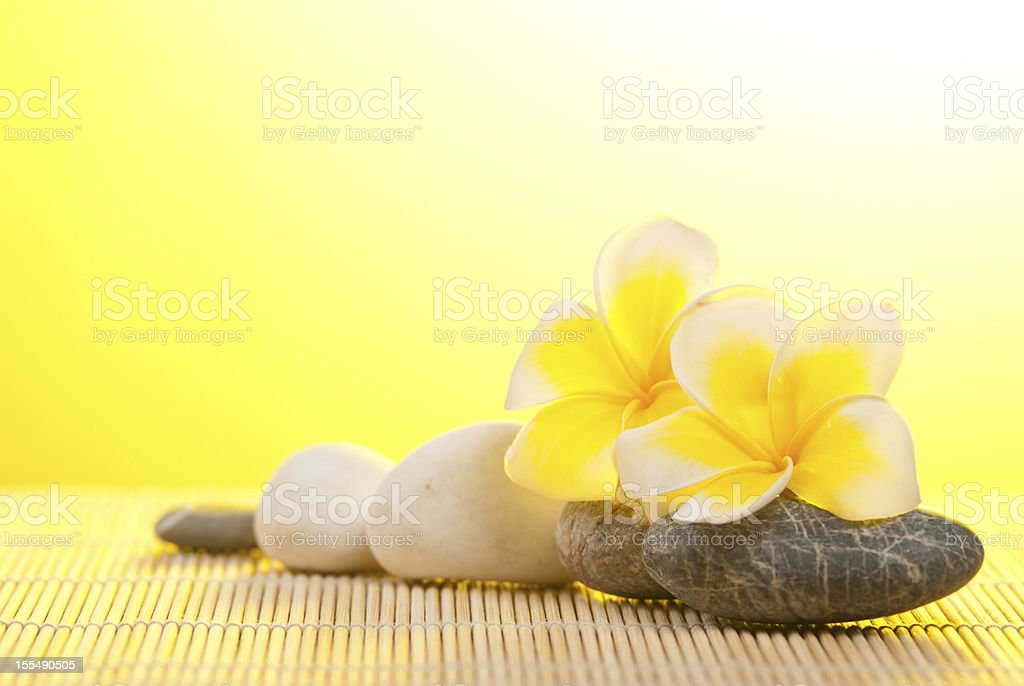 Leelawadee flower and pebbles on bamboo background royalty-free stock photo