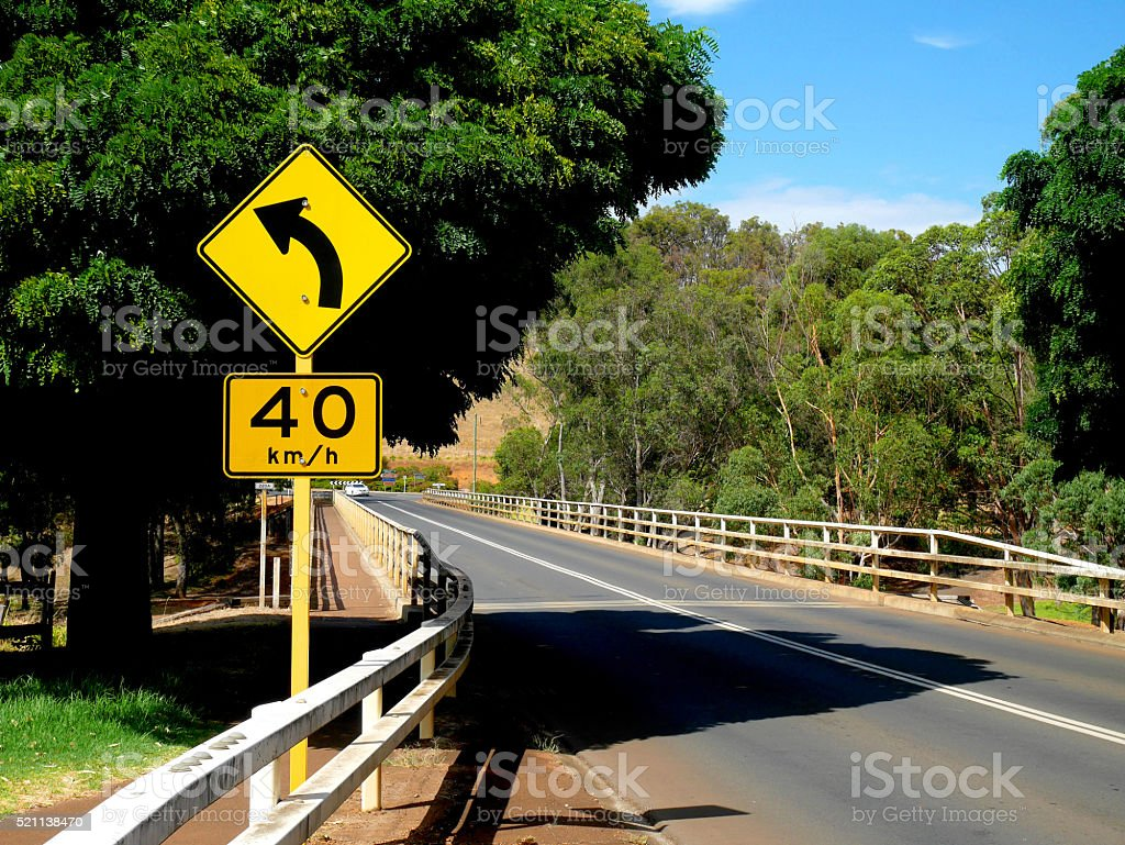 Left curve ahead sign and speed limit sign stock photo