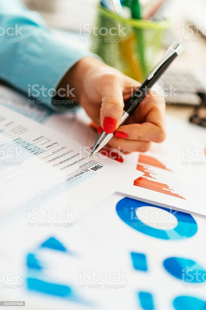 Left handed businesswoman with financial figures and tax form stock photo
