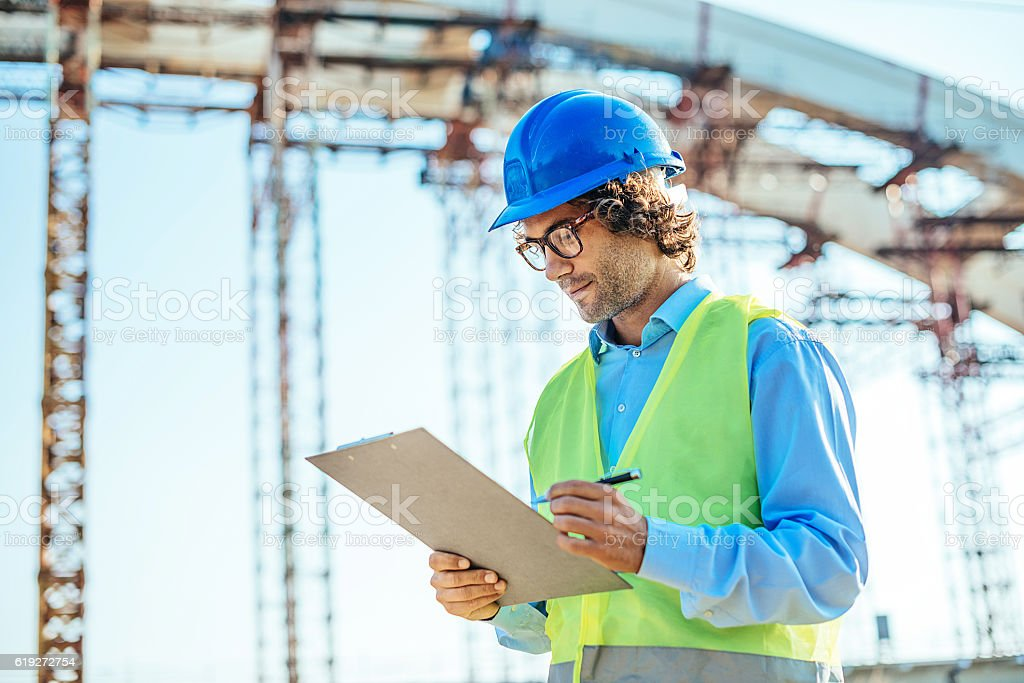 Left handed engineer signing contract stock photo