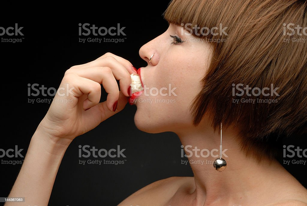 Left profile of girl putting candy into her mouth royalty-free stock photo
