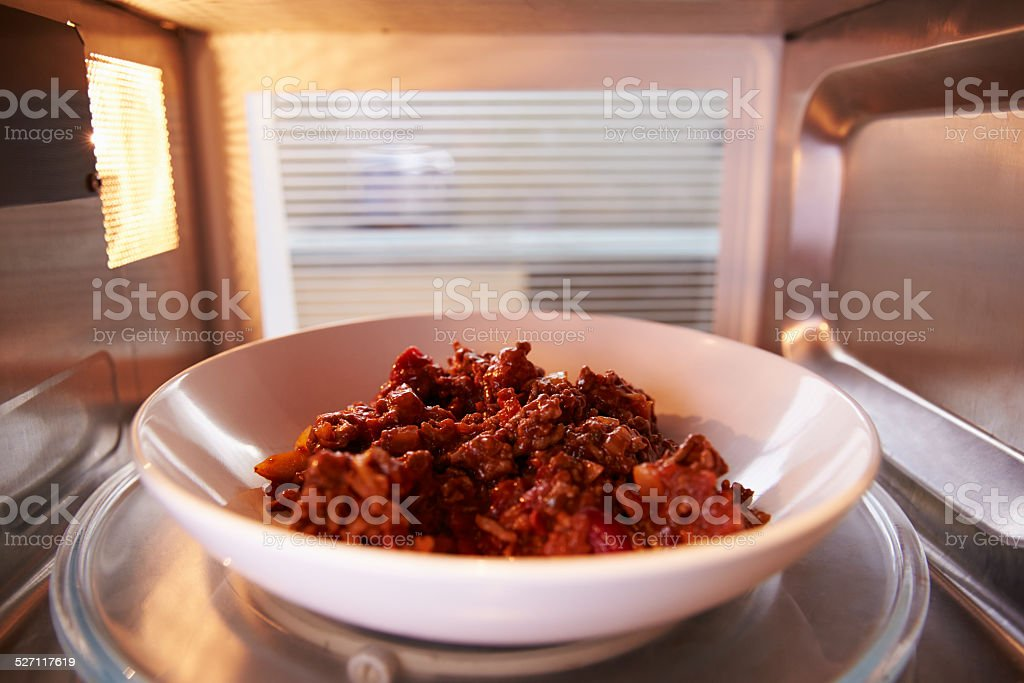 Leftover Chili Cooking Inside Microwave Oven stock photo