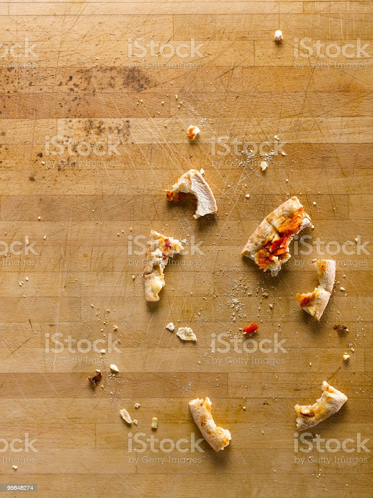 Leftover pizza crumbs scattered on a wooden table stock photo