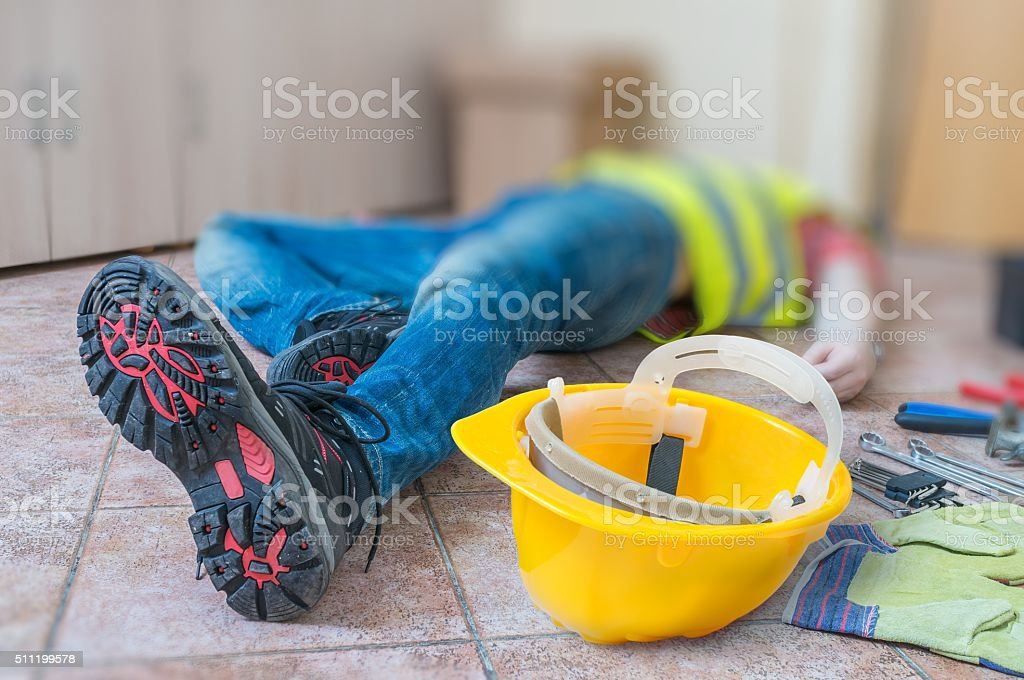 Leg and yellow helmet of injured lying worker at work. stock photo