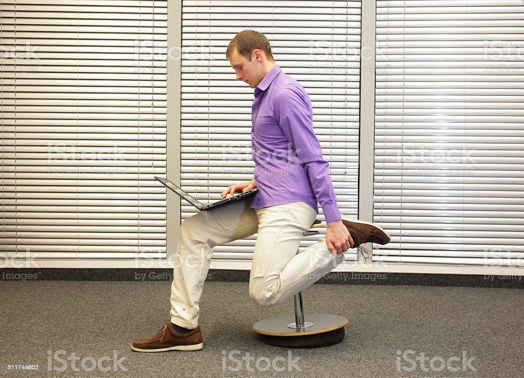 leg exercise during office work stock photo