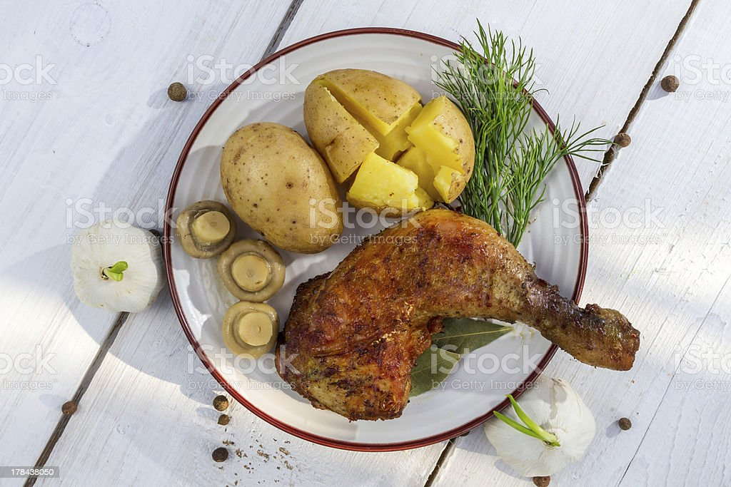 Leg of chicken served with potatoes in jackets royalty-free stock photo