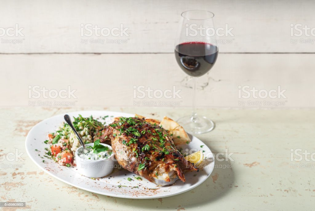 Leg of lamb baked with sauce in the white plate closeup with a side dish of rice. Rustic wooden table and a glass of red wine. stock photo