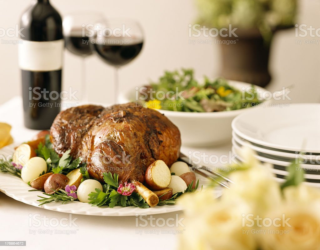 Leg of Lamb with potatoes, greens, and red wine. stock photo