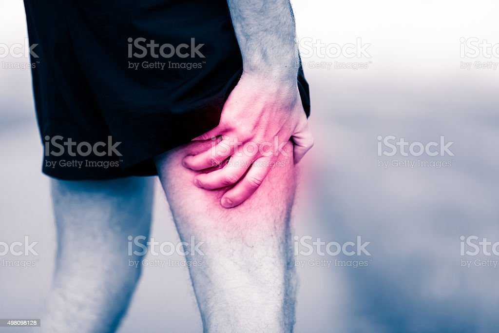 Leg pain, man holding sore and painful muscle stock photo