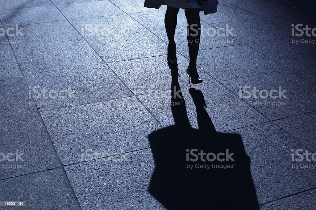 Leg view of a woman in heels walking at night with shadow stock photo