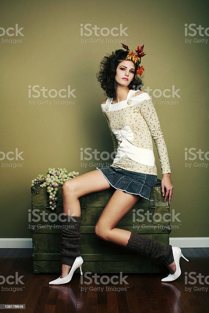 Leg Warmer Girl with Leaves in Hair on Wood Chest stock photo