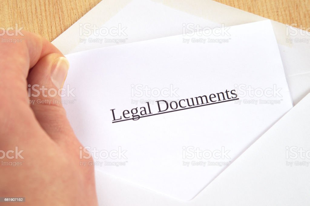 Legal Documents printed on white paper and envelope, hand holding it, wooden background stock photo