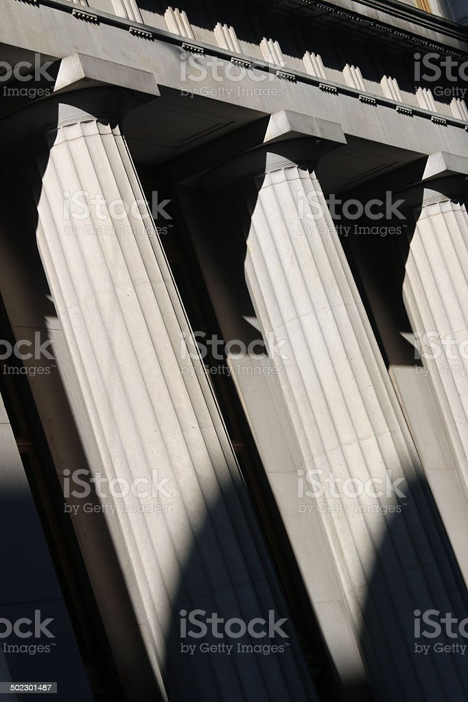 Legal pillars with sharp shadows stock photo