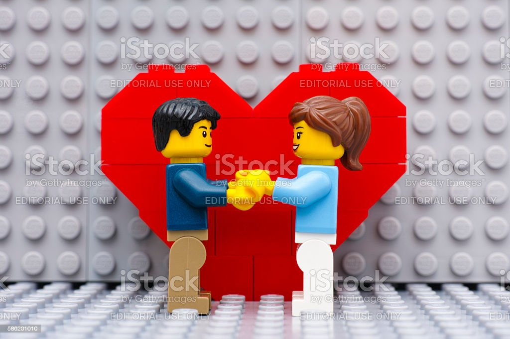 Lego couple standing in front of heart stock photo