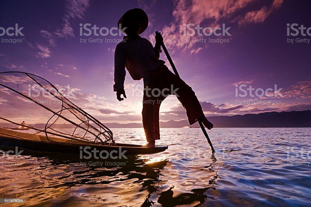 Leg-rowing fisherman on Inle Lake dirung sunset, Myanmar stock photo