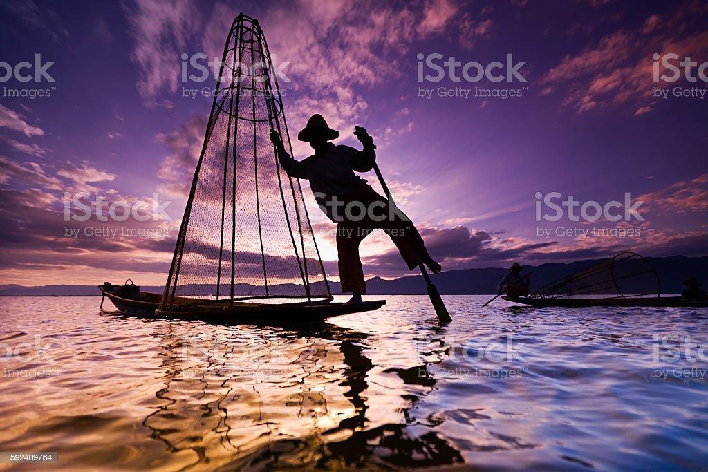 Leg-rowing fisherman on Inle Lake during sunset, Myanmar stock photo