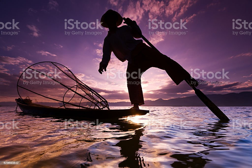 Leg-rowing fisherman on Inle Lake during sunset, Myanmar stock photo