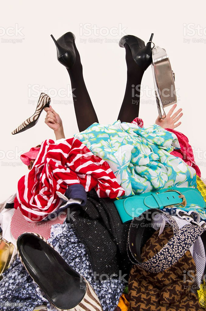 Legs and hands reaching from a big pile of clothes. stock photo