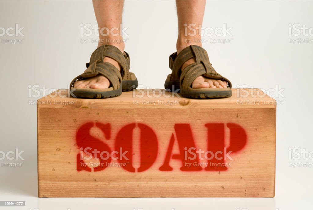 Legs and Sandals on Soapbox stock photo