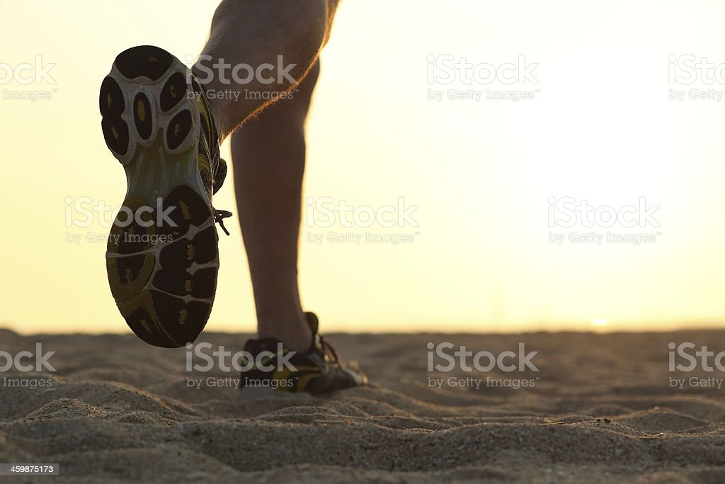 Legs and shoes of a man running at sunset stock photo