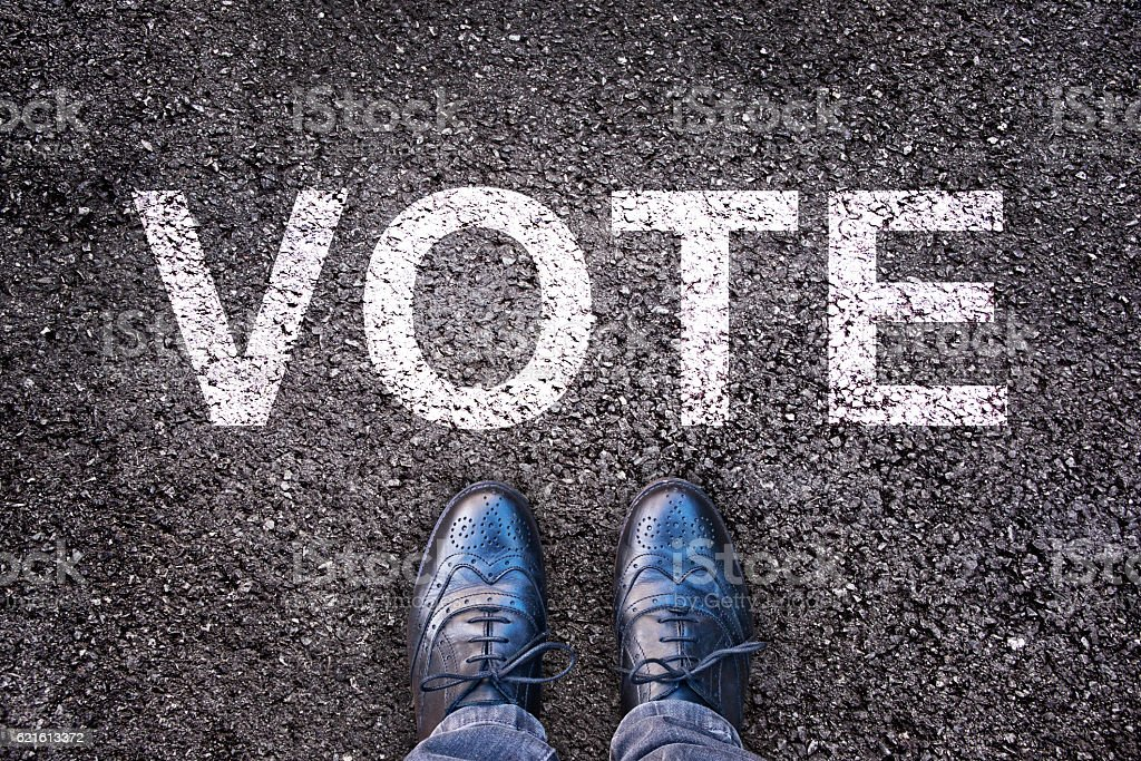 Legs and shoes on asphalt with the word 'vote' stock photo