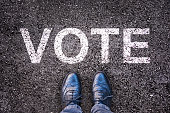 Legs and shoes on asphalt with the word 'vote'