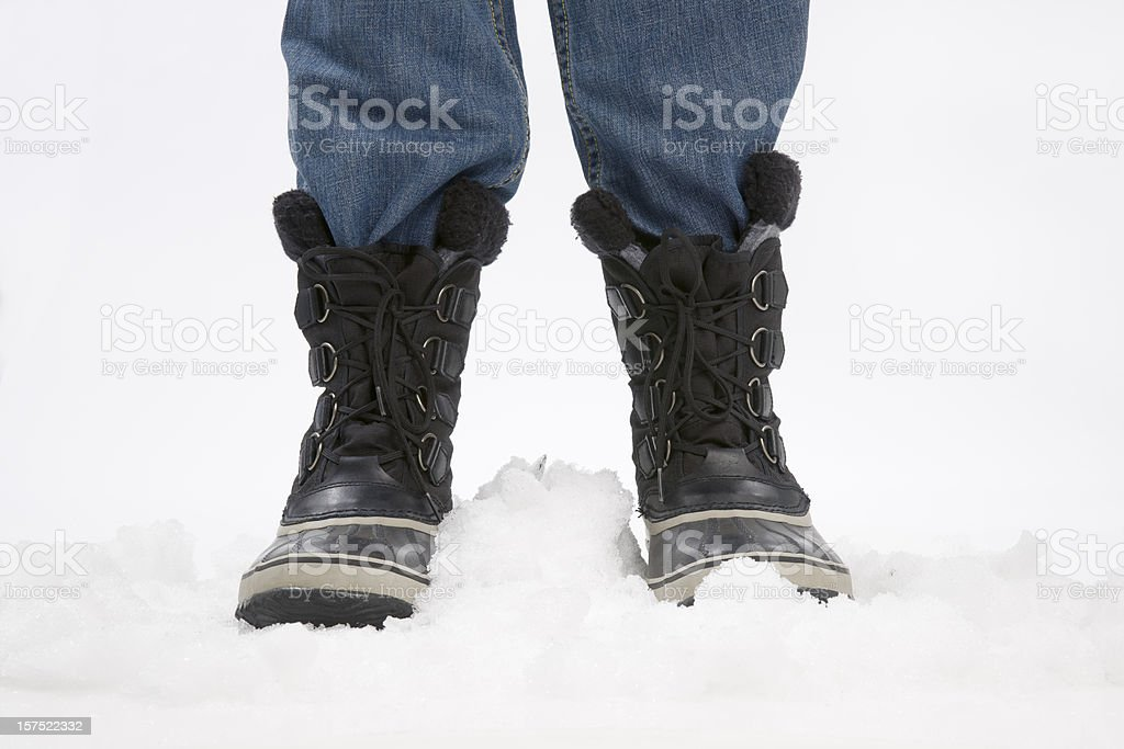 Legs and snow boots on ice stock photo