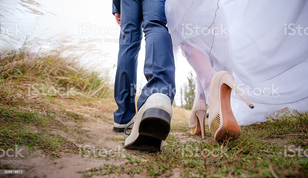 Legs brides and groom, newlyweds walk in the outdoors stock photo