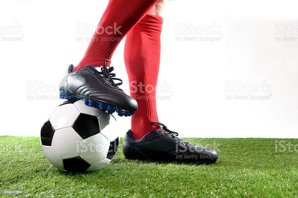 legs feet of football player playing with ball on grass stock photo