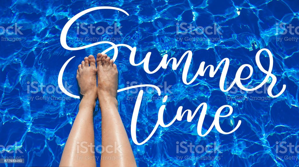 legs girl on a background of pool water and text Summer time. Calligraphy lettering hand draw stock photo
