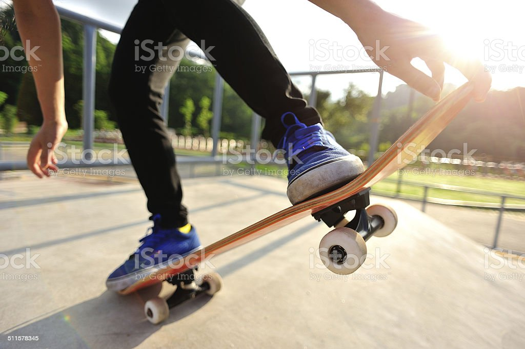 Legs in sneakers on a skateboard stock photo
