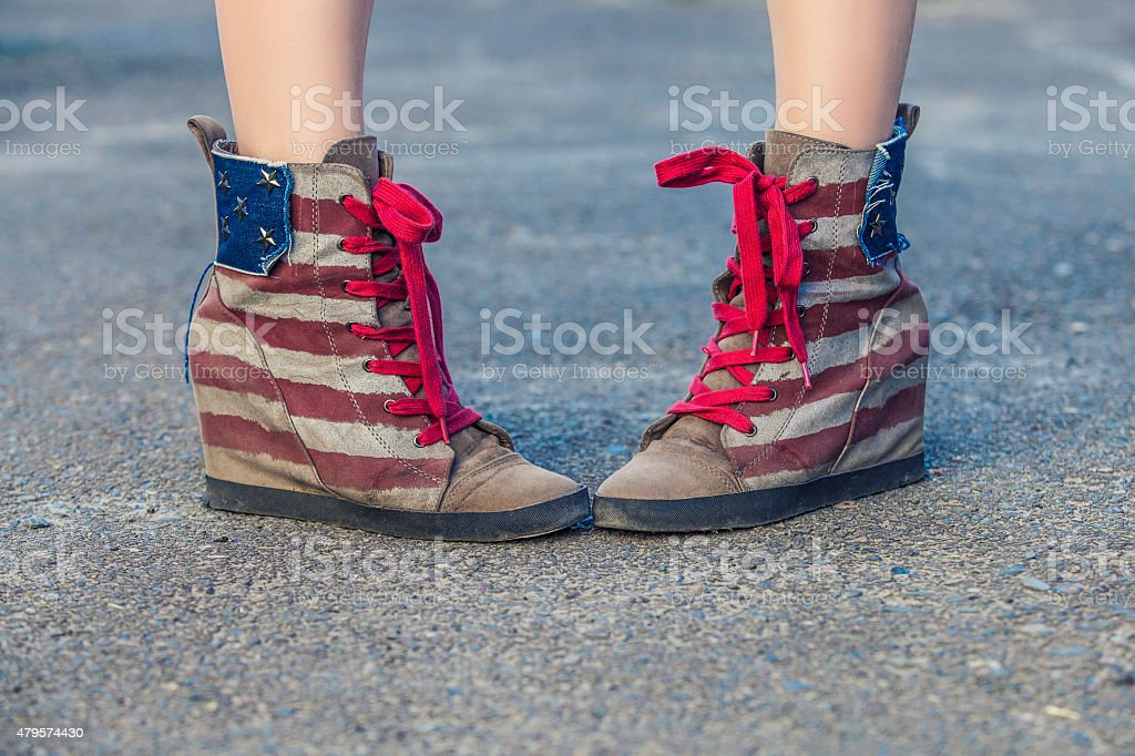 Legs in sneakers with the design of the American flag stock photo